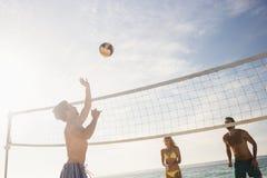 Amigos que jogam o voleibol da praia imagens de stock