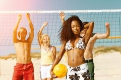 Amigos que jogam o voleibol de praia Foto de Stock