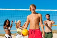 Amigos que jogam o voleibol de praia Fotografia de Stock