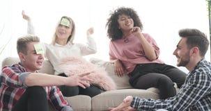 Amigos que juegan al juego de la nota de post-it en sala de estar metrajes