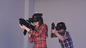Amigos que juegan al juego de la pistola de VR con los armas y los vidrios de la realidad virtual Foto de archivo