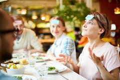 Amigos que juegan al juego en restaurante imágenes de archivo libres de regalías