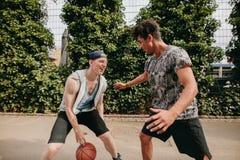 Amigos que juegan a baloncesto en corte Imágenes de archivo libres de regalías