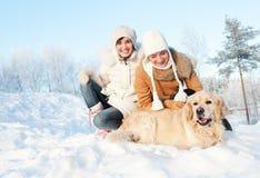 Amigos que juegan con el perro perdiguero de oro Fotos de archivo