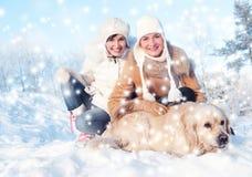 Amigos que juegan con el perro perdiguero de oro Imagen de archivo