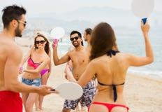 Amigos que juegan con las estafas en la playa Foto de archivo libre de regalías