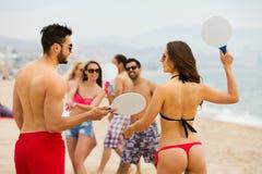 Amigos que juegan con las estafas en la playa Fotografía de archivo libre de regalías