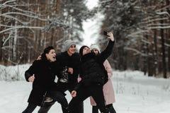 Amigos que juegan con nieve en parque imagen de archivo libre de regalías