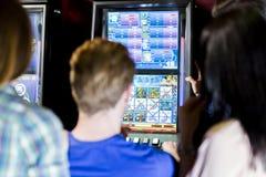 Amigos que juegan en un casino que juega la ranura y las diversas máquinas Imagen de archivo libre de regalías
