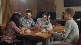 Amigos que juegan etiquetas engomadas en café Fotos de archivo