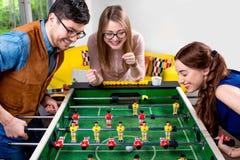 Amigos que juegan a fútbol de la tabla imagenes de archivo