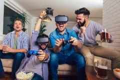 Amigos que juegan a los videojuegos con los vidrios de la realidad virtual - gente joven que se divierte con la consola de la nue fotografía de archivo libre de regalías