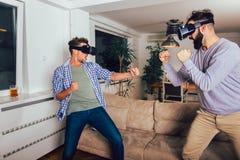 Amigos que juegan a los videojuegos con los vidrios de la realidad virtual - gente joven que se divierte con la consola de la nue fotos de archivo libres de regalías