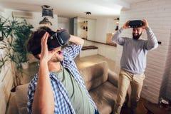Amigos que juegan a los videojuegos con los vidrios de la realidad virtual - gente joven que se divierte con la consola de la nue foto de archivo