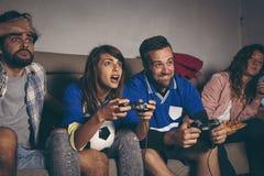 Amigos que juegan a un videojuego del fútbol imagen de archivo