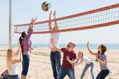 Amigos que juegan a voleibol en la playa Foto de archivo