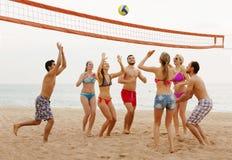 Amigos que lanzan la bola sobre red y la risa Fotografía de archivo libre de regalías