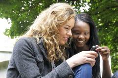 Amigos que leen el mensaje de texto en el teléfono móvil Imagen de archivo libre de regalías