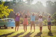Amigos que levantam suas mãos no parque fotos de stock