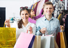Amigos que llevan bolsos en boutique Foto de archivo