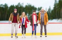 Amigos que llevan a cabo las manos en pista de patinaje al aire libre Imagenes de archivo
