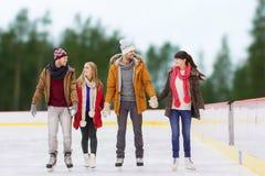 Amigos que llevan a cabo las manos en pista de patinaje al aire libre Imágenes de archivo libres de regalías