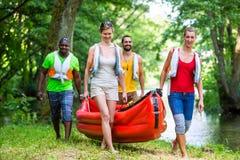 Amigos que llevan el kajak al río en bosque Imagenes de archivo