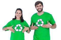 Amigos que llevan reciclando las camisetas que se señalan Foto de archivo libre de regalías