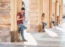 Amigos que mandan un SMS con smartphones Foto de archivo