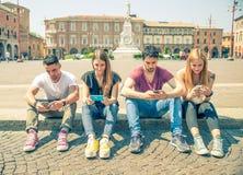 Amigos que mandan un SMS con smartphones Imágenes de archivo libres de regalías