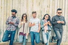 Amigos que mandan un SMS con smartphones Fotografía de archivo