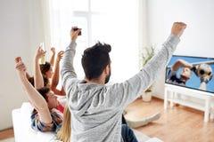 Amigos que miran el juego del fútbol o de fútbol en la TV Imágenes de archivo libres de regalías
