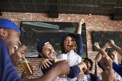 Amigos que miran el juego en barra de deportes en las pantallas que celebran foto de archivo libre de regalías