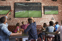 Amigos que miran el juego en barra de deportes en las pantallas que celebran fotografía de archivo libre de regalías