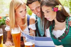 Amigos que miran el menú de las bebidas Imágenes de archivo libres de regalías