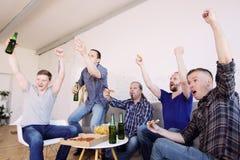 Amigos que miran el partido de fútbol que gana imagen de archivo libre de regalías