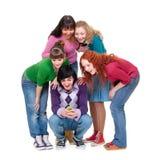 Amigos que miran el teléfono celular y la risa Fotos de archivo