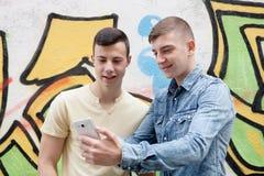 Amigos que miran el teléfono en la calle Imagen de archivo libre de regalías