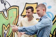 Amigos que miran el teléfono en la calle Imágenes de archivo libres de regalías