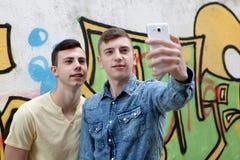 Amigos que miran el teléfono en la calle Imagen de archivo