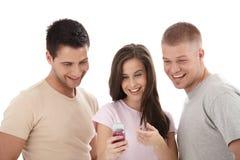 Amigos que miran el teléfono celular junto, riendo Fotos de archivo