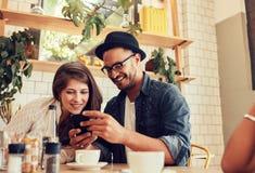 Amigos que miran el teléfono móvil mientras que se sienta en café Imagen de archivo