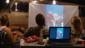 Amigos que miran el vídeo con el proyector en sitio para acampar almacen de metraje de vídeo