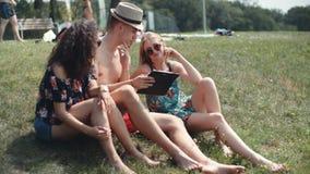 Amigos que miran en su tableta en la playa almacen de video