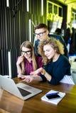 Amigos que miran la computadora portátil junto Discuta o mirando alguno interesante en el ordenador portátil, la diversión y emoc Foto de archivo libre de regalías