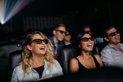 Amigos que miran la película 3d y la risa foto de archivo