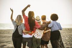 Amigos que miran la puesta del sol en la playa imágenes de archivo libres de regalías