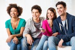 Amigos que miran la televisión Foto de archivo libre de regalías