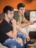 Amigos que miran la televisión en casa Fotografía de archivo libre de regalías