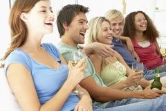 Amigos que miran la televisión junto Foto de archivo libre de regalías